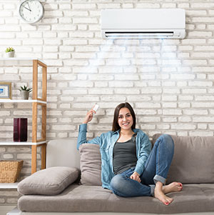Woman enjoying her A/C Unit at home