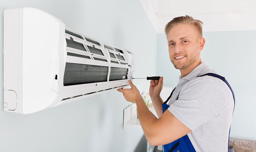 Man using screwdriver on A/C Unit
